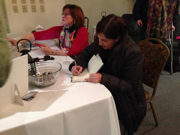 "Alumna Helen Peppe signs books after the alumni reading. Helen's new book ""Pigs Can't Swim"" is out from Da Cappo Press in February"