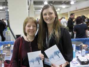 eanne Marie helps SC alum Lexa Hillyer display her prize-winning book Acquainted with the Cold at AWP Boston.